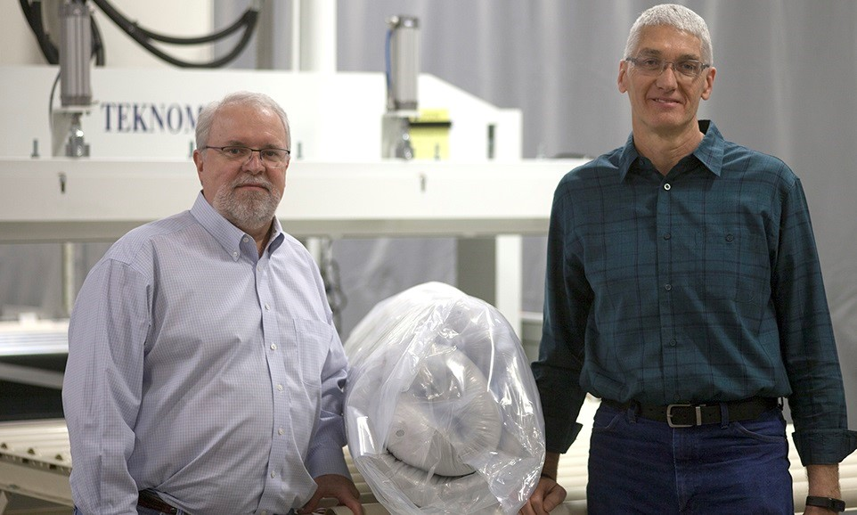 Tony Garrett, President of GSG, and Terry Myers, Director of Engineering, with a Teknomac machine and roll-pack mattress.