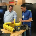 Flex-O-Lators Vision Tech Lead, Ken Schramm, describes a robotic arm to Jason Gorham.