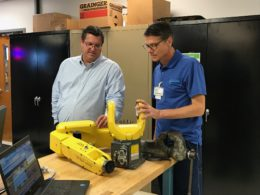 Flex-O-Lators Vision Tech Lead, Ken Schramm, describes a robotic arm to Jason Gorham.