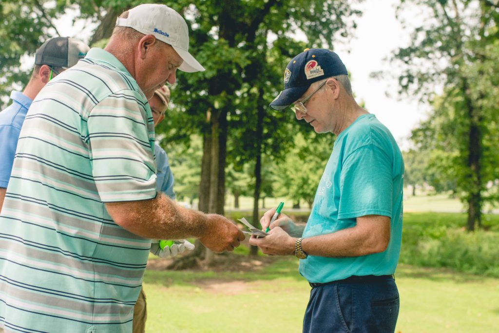 David Austin from L&P assists a golfer with the poker tournament.